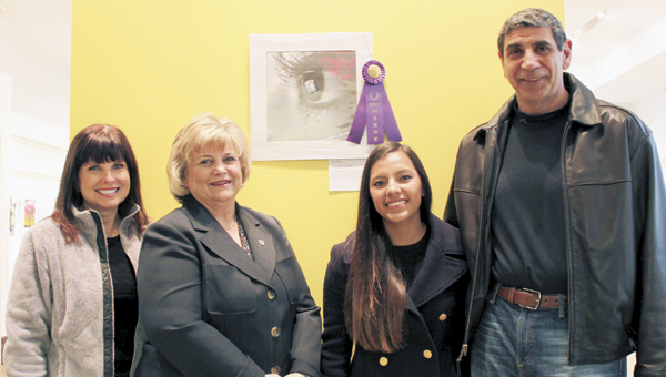 Grace Haddad, second from right, poses with her Best in Show-winning art, on the wall behind her, along with her parents, Mary and Lou Haddad, and Mayor Linda T. Johnson, who presented the awards in the Suffolk Sister Cities Young Artists and Authors Showcase at the Suffolk Center for Cultural Arts in March. Haddad and another Suffolk entrant, Kiraney Zhang, have been named nationwide finalists in the competition.