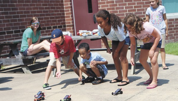 Josh Finley, Logan Harris, Regina Warren and Raleigh Aigner race solar-powered cars during the Tidewater Regional Governor's School at King's Fork Middle School Thursday.