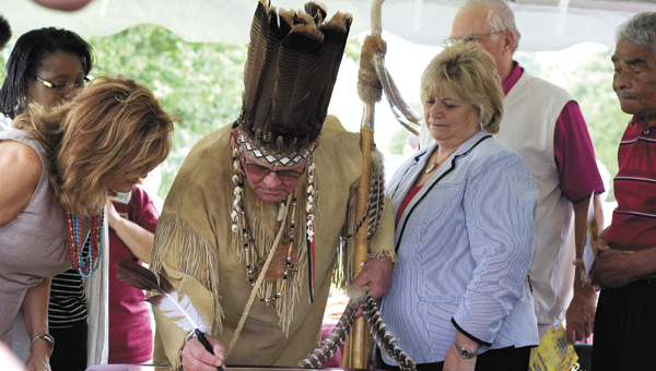 Chief Barry Bass of the Nansemond Indian Tribal Association signs a ceremonial document commemorating the land transfer from the city to the tribe. Looking on are, from left, City Manager Selena Cuffee-Glenn, Media and Community Relations Director Diana Klink, Mayor Linda T. Johnson and Councilmen Jeffrey Gardy and Curtis Milteer.