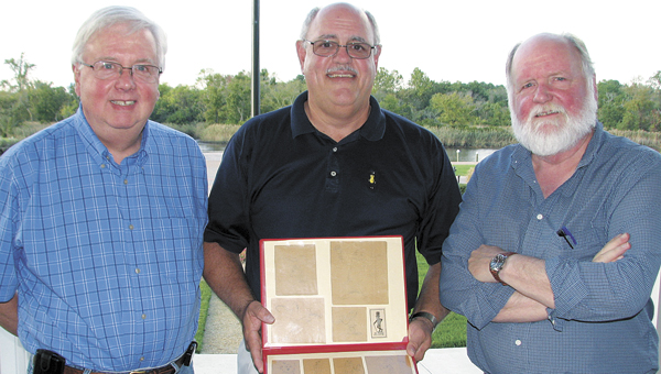 From left, Charlie Lewis, Bob Slade and Peyton Lewis, nephews of Mr. Peanut creator Antonio Gentile, show off the original drawings by their uncle, a Suffolk native, that transformed into one of the world's best-known advertising icons.