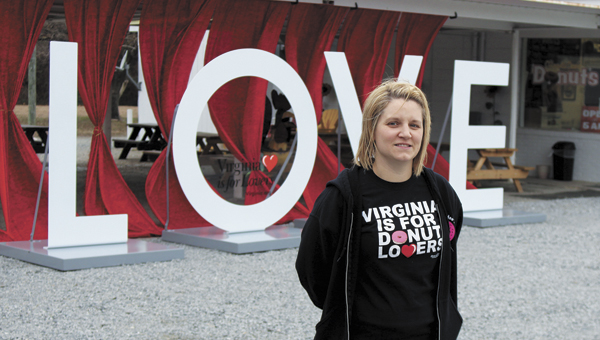 """O'doodleDoo's owner Reeva Luecke is excited to host the Virginia Tourism Corporation's """"LOVE"""" sign at her Bridge Road shop through the Valentine's Day weekend. She said she thought it would be a fun thing to do for the community."""