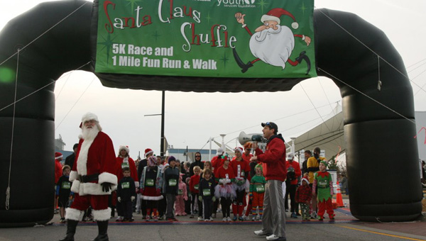 Festive cardio: Dan Clements of Suffolk serves as Santa Claus, while WVEC meteorologist Craig Moeller talks to a crowd of costumed runners at a previous edition of the Santa Claus Shuffle 5K Race and One Mile Fun Run & Walk. The latest edition will be held on Dec. 13. Photo submitted by Jeannie Martin