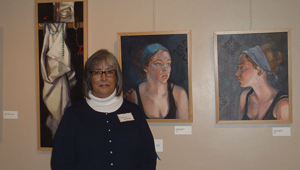 Corinne Lilyard-Mitchel, above, is shown with her first-place winning oil paintings at the Suffolk Art Gallery during the Suffolk Art League's Annual Juried Exhibition opening reception.