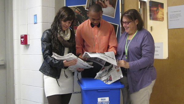 Paul D. Camp Community College students Danielle Stauffer and Trey Cofield and grants writer Patricia Bills prepare to recycle copies of the Suffolk News-Herald in one of the new recycling bins at the college provided through a grant.