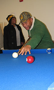 James Scott tries out the new pool tables in the game room at the Whaleyville Community Center following Friday's ceremony.