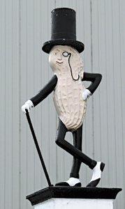 Several statues of Mr. Peanut, the advertising icon created in Suffolk, line the perimeter of the Planters Peanuts processing plant near downtown Suffolk. Kraft, which owns Planters, announced on Wednesday a plan to merge with Heinz.