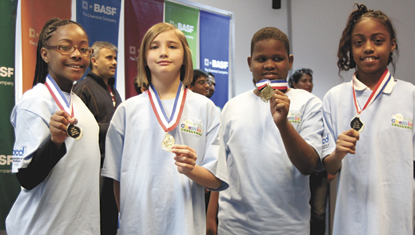 Mack Benn Jr. Elementary School's Ariyahna Cheeks and Thalia Bonte, as well as Jamauri Demiel and Jaylen Daughtrey of Booker T. Washington Elementary School, hold out their medals after the Virginia You Be The Chemist Challenge, held at BASF in Suffolk on Saturday.