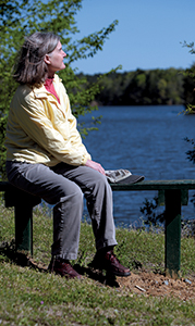 """Susan Andrews and her husband """"Biff"""" like to walk along the road and trails at Lone Star Lakes at least once a week. There are many places to sit down and enjoy the views, like this bench at Crane Lake."""