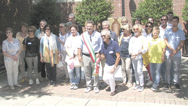 Members of the exchange group from Oderzo, Italy, and the surrounding areas pause their downtown tour on Thursday for a photo in front of the Obici-Oderzo Fountain near the Godwin Courts Building.