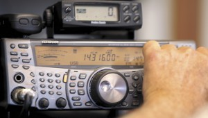 Buck Johnson turns the knob on his ham radio equipment, looking for a contact in another country. He eventually got one from Italy.