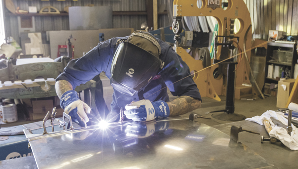 Kyle Yocum welds the skirt on a door panel created from scratch in his shop on Progress Road.