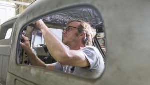 Eric Mickelson goes over his work carefully after having pulled a dent out of the inside of a truck cab at Yocum's Signature Hot Rods on Progress Road.