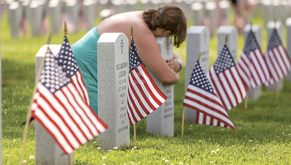 Kayla Osiecki of Suffolk takes a moment to grieve at the grave of her grandfather, a U.S. Navy veteran who died in 2011. Kayla and her mother helped place the thousands of flags that stand in front of the gravesites at the cemetery this weekend.
