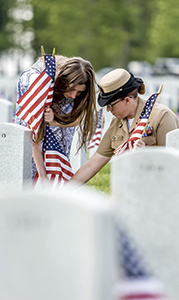 U.S. Navy Chief Fire Controlman Sharon Heisler of Suffolk kneels with her daughter, Christine Clark, in front of a grave marker at the Albert G. Horton Jr. Memorial Veterans Cemetery on Friday. They were two of the dozens of volunteers that helped place flags for Monday's Memorial Day ceremony there.
