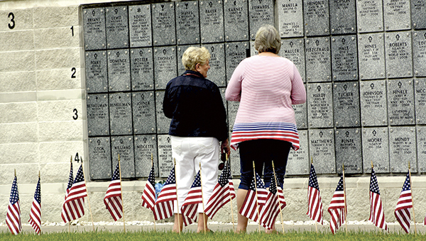 Paulette Moore and Paula Adolph search the columbarium for a loved one's name at the Albert G. Horton Jr. Memorial Veterans Cemetery on Monday following a Memorial Day ceremony.