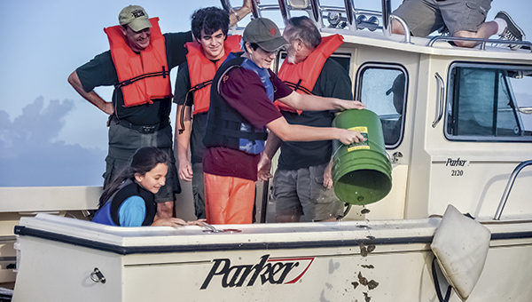 Cameron Bruce, surrounded by family and friends who helped with his Eagle project, drops oysters onto a protected reef in the Elizabeth River.