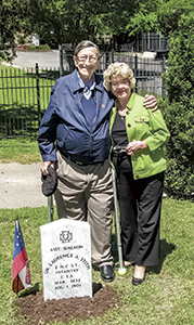 Laurence Stith and his wife, Jean Stith, pose for a photo at the new headstone of Dr. Laurence A. Stith, his great-grandfather, at Cedar Hill Cemetery on Saturday.