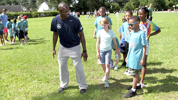 Keith Ricks,  a King's Fork High School graduate and 2016 Olympic hopeful, shows a class of Kilby Shores Elementary School students how to do the long jump during their field day on Monday.