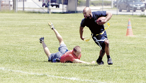 Antonio Diggs of the Suffolk Police Department evades a tackle attempt by Steven Speight of the Suffolk Department of Fire and Rescue during a flag football game in 2013.