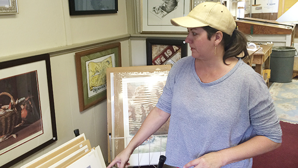 Marlene Nierman, manager of Crittenden Gallery and Frame Shop, displays the effect a good frame can have on a work of art. Nierman took over as manager in April.