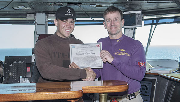 Aviation Electronics Technician 3rd Class Nathan Potter, left, receives recognition as Warrior of the Day from Capt. Ryan B. Scholl on the bridge of aircraft carrier USS Harry S. Truman. (Mass Communication Specialist 3rd Class Anthony Flynn/U.S. Navy)