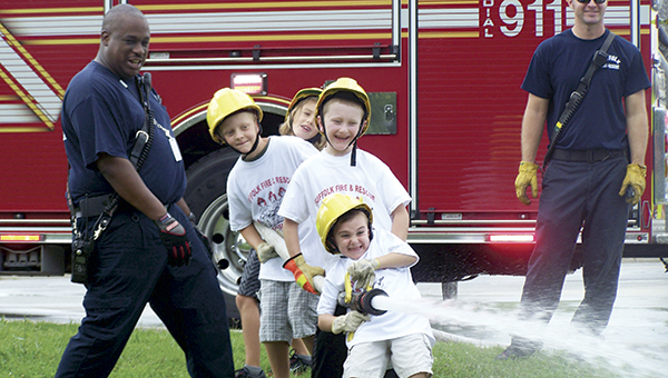 Participants in a prior Fire and Life Safety Camp learn to aim a firehose. (City of Suffolk Photo)