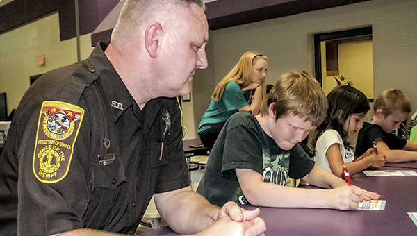 Suffolk Sheriff's Deputy Mike Ambrose watches as students, including Julian Lindblad, sign a pledge to be safe around pools this summer.