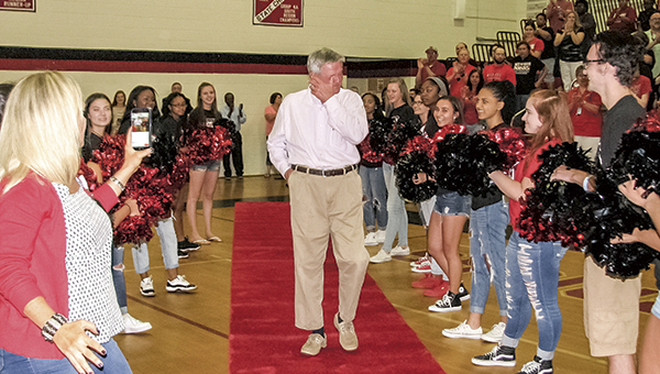 Thomas McLemore reacts to a gymnasium full of chanting students as he walks a red carpet flanked by cheerleaders during his last school day as principal of Nansemond River High School on Friday.