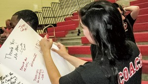 Jennifer Dye, one of the school's alumni who planned the event, signs a giant card for McLemore.