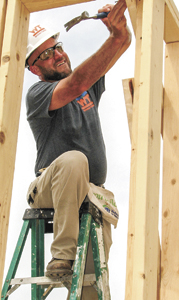 Scott Downey drives a nail in the house under construction.