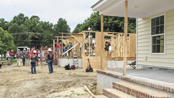 Construction crews work on a Habitat for Humanity home on Lake Kennedy Drive Wednesday, with a completed home in the foreground.
