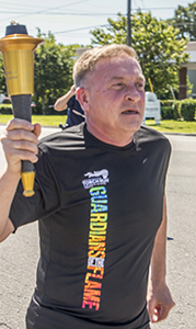 Major Gerald Brandsasse of the Suffolk Police Department holds the Olympic Flame of Hope after taking the handoff from a Portsmouth police officer during the Law Enforcement Torch Run Thursday in support of Special Olympics Virginia. Brandsasse and about 15 other public safety officers carried the torch in shifts on their way along Bridge Road to the Isle of Wight County line.
