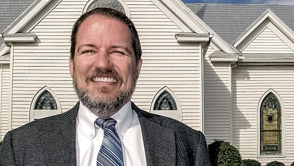 The Rev. Gregory Ryan stands in front of Oakland Christian United Church of Christ in 2013, shortly after he was officially installed as pastor. Ryan has been diagnosed with leukemia and is being treated at Duke University Hospital.