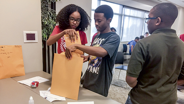 Aniyah Parker, Lamar Jones and Lashawn Scott put evidence from their mock crime scene into an envelope so it can be analyzed. Their group dusted for fingerprints and used DNA analysis to solve their case.
