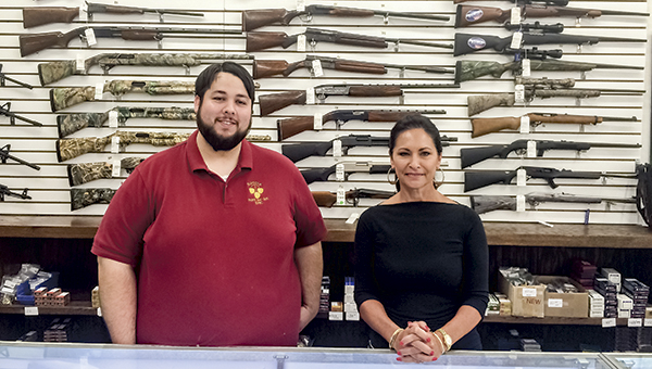 Eric Symborski, assistant manager, and Joanna Erwin, owner of Suffolk Pawn and Gun, show off a selection of firearms available in their shop. Symborski is skeptical about a bill that would deny firearms to those on the terrorist watch list, saying that some people on the list don't deserve to be there.