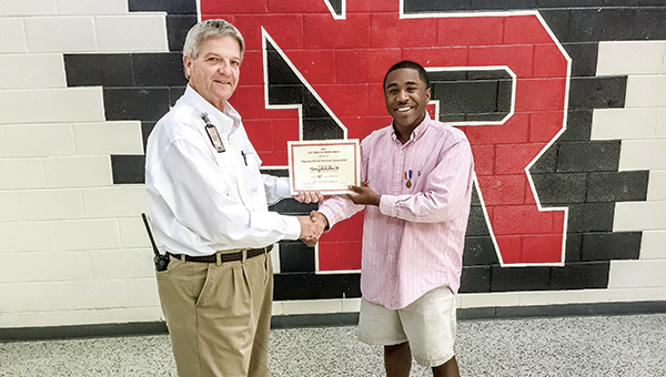 Nansemond River High School Principal Thomas McLemore presents Rodney McKeithan with his All-Virginia Certification and Medal at the school.