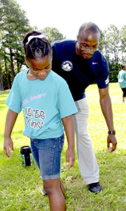 Keith Ricks, a King's Fork High School graduate and 2016 Olympic hopeful, and Li'Niya Richardson look down at a tape measure to see how many feet Li'Niya's long jump was during Kilby Shores Elementary School's field day on Monday. Ricks was a participant in a program meant to inspire young people through sports.