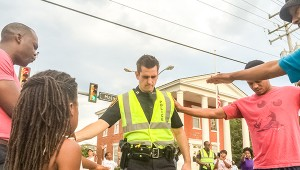 Demonstration organizers, including Domenick Epps, at left, pray with Officer T.A. Smith of the Suffolk Police Department in the intersection of North Main Street and Constance Road Monday evening.