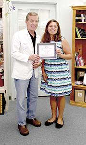 Lakeland High School graduate Ariel Salerno receives a Good Neighbor Pharmacy scholarship from Bennett's Creek Pharmacy owner Chris Jones.