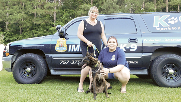 """Stephanie and Molly Cox and Apollo """"paws"""" for a photo at the Imperial K-9 S.T.A.R. Puppy training graduation. Apollo will be a service dog for Molly Cox, who battles epilepsy, PTSD and depression."""