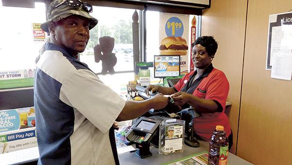 7-Eleven cashier Lulu Boonn sells Curtis Britt a Mega Millions ticket on Thursday.