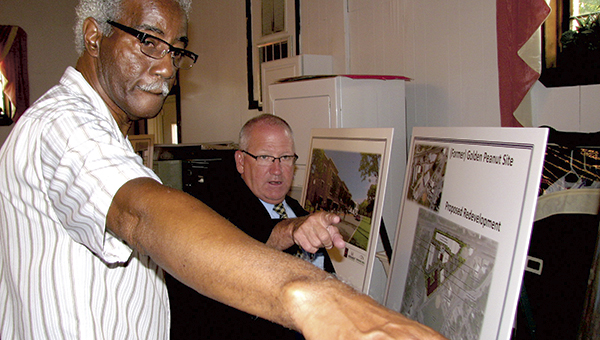Saratoga resident Alfred Colander and Deputy City Manager Scott Mills look at a display regarding the Monument Companies' project at the former Golden Peanut site during a community meeting Thursday at Faith Temple Apostolic Church.
