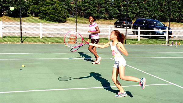 Olivia Hodouto, 10, and Erica Walker, 13, participate in a recent tennis lesson offered by Suffolk Parks and Recreation.