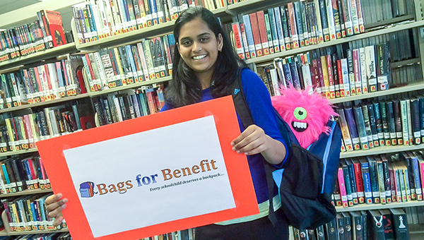 """Archana Venkatesan, 14, founder of """"Bags for Benefit,"""" (and the Suffolk Library mascot, Fred), is collaborating with the city's libraries to collect backpacks for homeless children."""