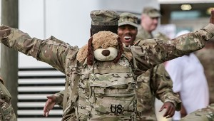 A guardsman has a ride-along friend on his pack as he prepares to hug a fellow soldier before heading home.