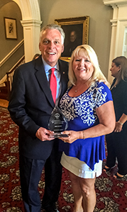 Trish Adams receives an award for promoting motorcycle safety from Gov. Terry McAuliffe at a June 28 event.