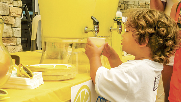 Gideon Thompson, 3, pours a glass of lemonade for a customer at his lemonade stand in Harbour View on Saturday.
