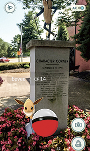 A wild Eevee appears in front of a statue of Mr. Peanut. Pokemon GO projects the creatures onto a real backdrop to give players the feeling they are catching real Pokemon.