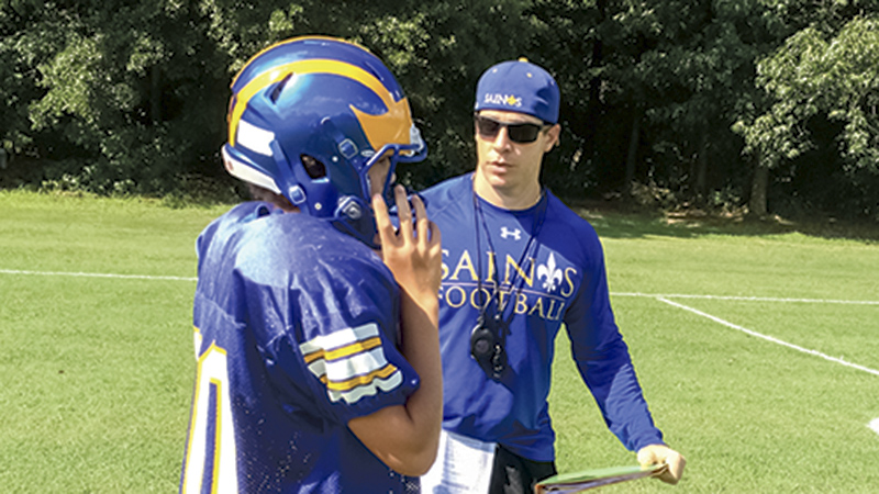 Nansemond-Suffolk Academy head football coach Mike Biehl speaks to one of his players during practice. Biehl said he is implementing a new offensive strategy for the upcoming season.
