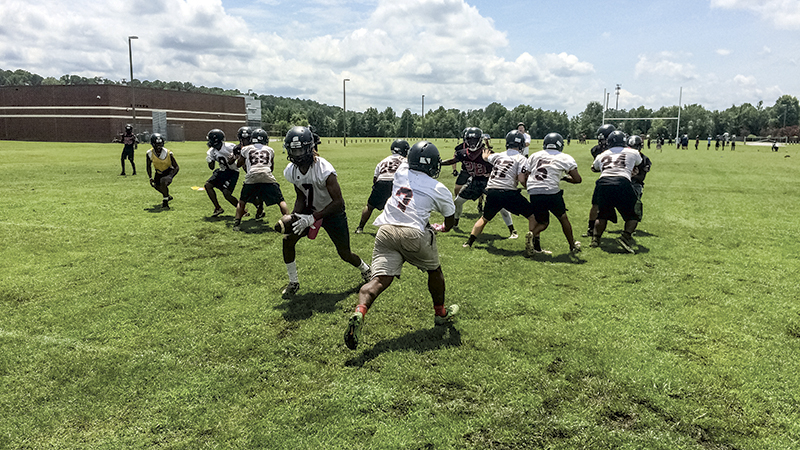 Nansemond River High School's football team ran plays at practice, despite the hot and muddy conditions. Coach David Coccoli kept his players hydrated with water stations, and even served the players water through their facemasks to make sure they did not overheat.